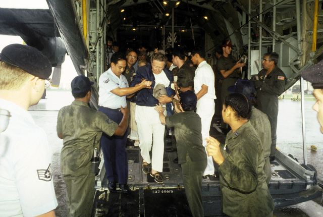 A victim of the Pines Hotel fire is helped off of a C-130 Hercules aircraft for transport to the Regional Medical Center. Over 200 World War II veterans and their families were staying at the hotel in Baguio while attending a reunion commemorating the 40th anniversary of the liberation of the Philippines