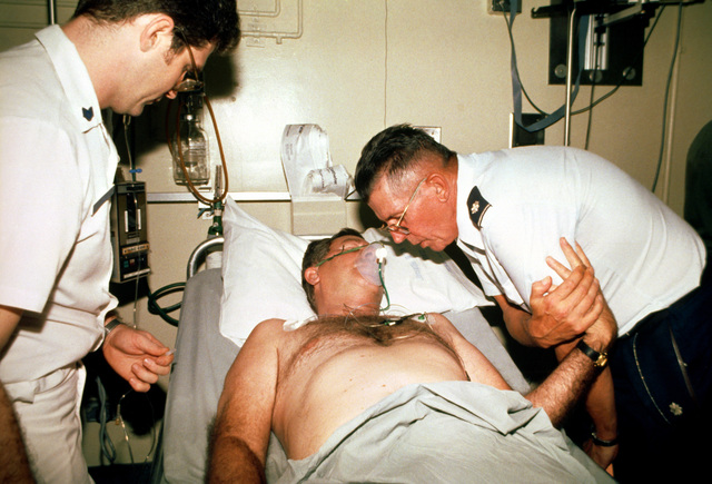 STAFF SGT. Floyd Jackson stands by while Chaplain (LT. COL.) Carl Bagge comforts a Pines Hotel fire victim at the Regional Medical Center. Over 200 World War II veterans and their families were staying at the hotel in Baguio while attending a reunion commemorating the 40th anniversary of the liberation of the Philippines