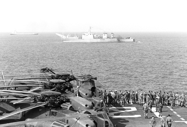 "Personnel aboard the amphibious assault ship USS INCHON (LPH 12) watch as the tank landing ship USS SUMTER (LST 1181) is utilized to rescue crewmen from the sinking Panamanian ship ""SKY ONE,"". CH-53D Sea Stallion helicopters are visible on the flight deck of the INCHON"