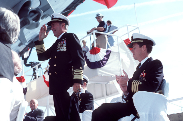 Admiral Wesley L. McDonald, Commander in CHIEF, Atlantic and Atlantic Fleet, salutes during the launching ceremony for the nuclear-powered aircraft carrier USS THEODORE ROOSEVELT (CVN 71). Seated next to Admiral McDonald is Captain Paul W. Parcells, prospective commanding officer of the carrier