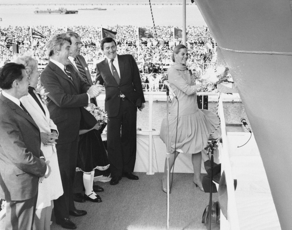 Mrs. Barbara Lehman, sponsor, breaks a champagne bottle on the bow of the nuclear-powered aircraft carrier USS THEODORE ROOSEVELT (CVN 71) during the christening ceremony at Newport News Shipbuilding ceremony at Newport News Shipbuilding ceremony at Newport News Shipbuilding and Drydock Company. The guests on the platform include Secretary of the Navy John Lehman, Jr., center, and Senator John Warner (R-VA), left