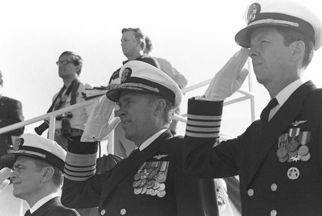 Saluting during the launching ceremony for the nuclear-powered aircraft carrier USS THEODORE ROOSEVELT (CVN 71) are, left to right, Admiral Kinnaird R. McKee, Director of the Naval Nuclear Propulsion Program; Admiral Wesley L. McDonald, Commander in CHIEF, Atlantic and Atlantic Fleet; and Captain Paul W. Parcels, prospective commanding officer of the carrier