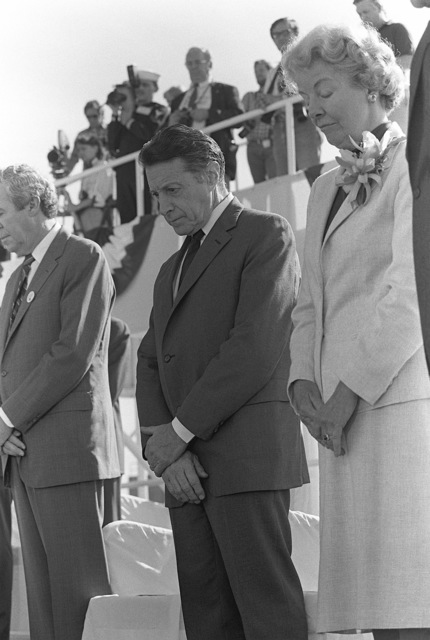 Secretary of Defense Caspar W. Weinberger bow his head during the invocation at the beginning of the launching ceremony for the nuclear-powered aircraft carrier USS THEODORE ROOSEVELT (CVN 71). With Weinberger are Edward J. Campbell, left, President and CHIEF Executive Officer of Newport News Shipbuilding, and Mrs. William McMillan, Matron of Honor