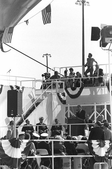 Senator John W. Warner, R-Virginia, addresses guests attending the nuclear-powered aircraft carrier USS THEODORE ROOSEVELT (CVN 71). Seated on the left are, left to right, William Johnston, President of the Theodore Roosevelt Association; Admiral James D. Watkins, CHIEF of Naval Operations; and Secretary of the Navy John F. Lehman Jr