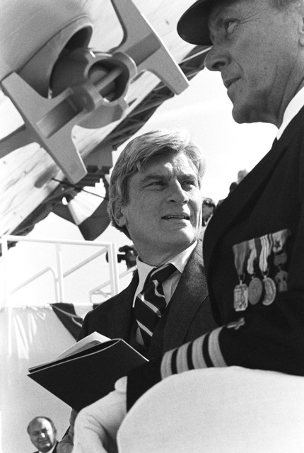 Senator John W. Warner, R-Virginia, speaks with Captain Robert J. Ecker, Chaplain Corps, US Navy Fleet Chaplain, US Atlantic Fleet, during the launching ceremony for the nuclear-powered aircraft carrier USS THEODORE ROOSEVELT (CVN 71)