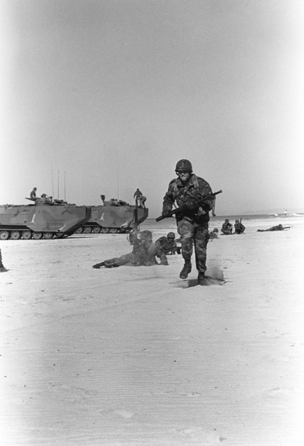 A member of Weapons Platoon, Co. C, 1ST Bn., 5th Marines, runs for cover during an amphibious assault training exercise at Delmar Beach. In the background are LVTP-7 tracked landing vehicles from Co. C, 1ST Amphibious Bn
