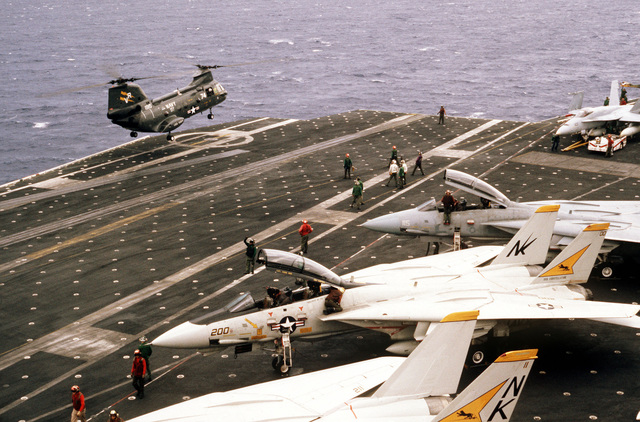 A UH-46D Sea Knight helicopter from the ammunition ship USS KISKA (AE 35) hovers above the flight deck of the aircraft carrier USS CONSTELLATION (CV 64) during Fleet Exercise 85. In the foreground are several F-14A Tomcat aircraft from Fighter Squadron 21. On the far right is an F/A-18A Hornet aircraft