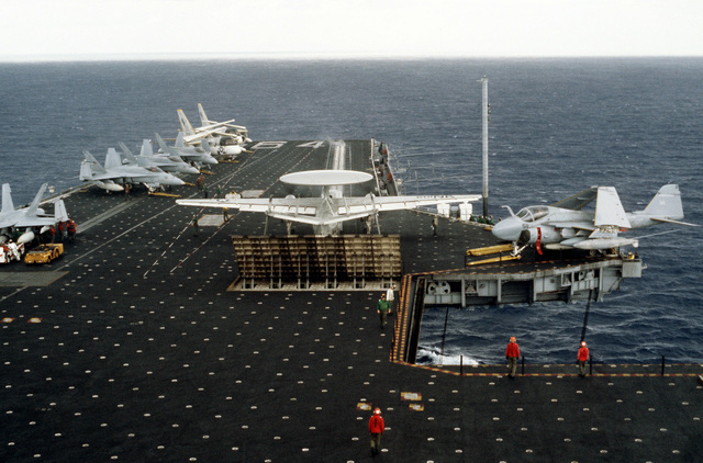 An E-2B Hawkeye aircraft is prepared for launch from the aircraft carrier USS CONSTELLATION (CV 64) during Fleet Exercise 85. A Mark-7 jet blast deflector is raised behind the aircraft. Parked on the flight deck are F/A-18A Hornets, S-3A Vikings, and an A-6E Intruder next to the lower elevator