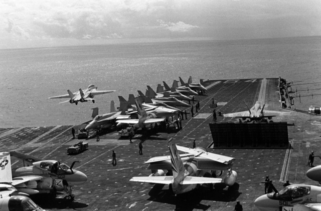 An F-14A Tomcat aircraft takes off from the aircraft carrier USS CONSTELLATION (CV 64) during Fleet Exercise 85. An F/A-18A Hornet is on a catapult in front of a Mark-7 jet blast deflector. Behind the deflector is an S-3A Viking aircraft with wings folded. Among the aircraft parked on the flight deck are S-3A`s, F/A-18A Hornets and A-6E Intruders