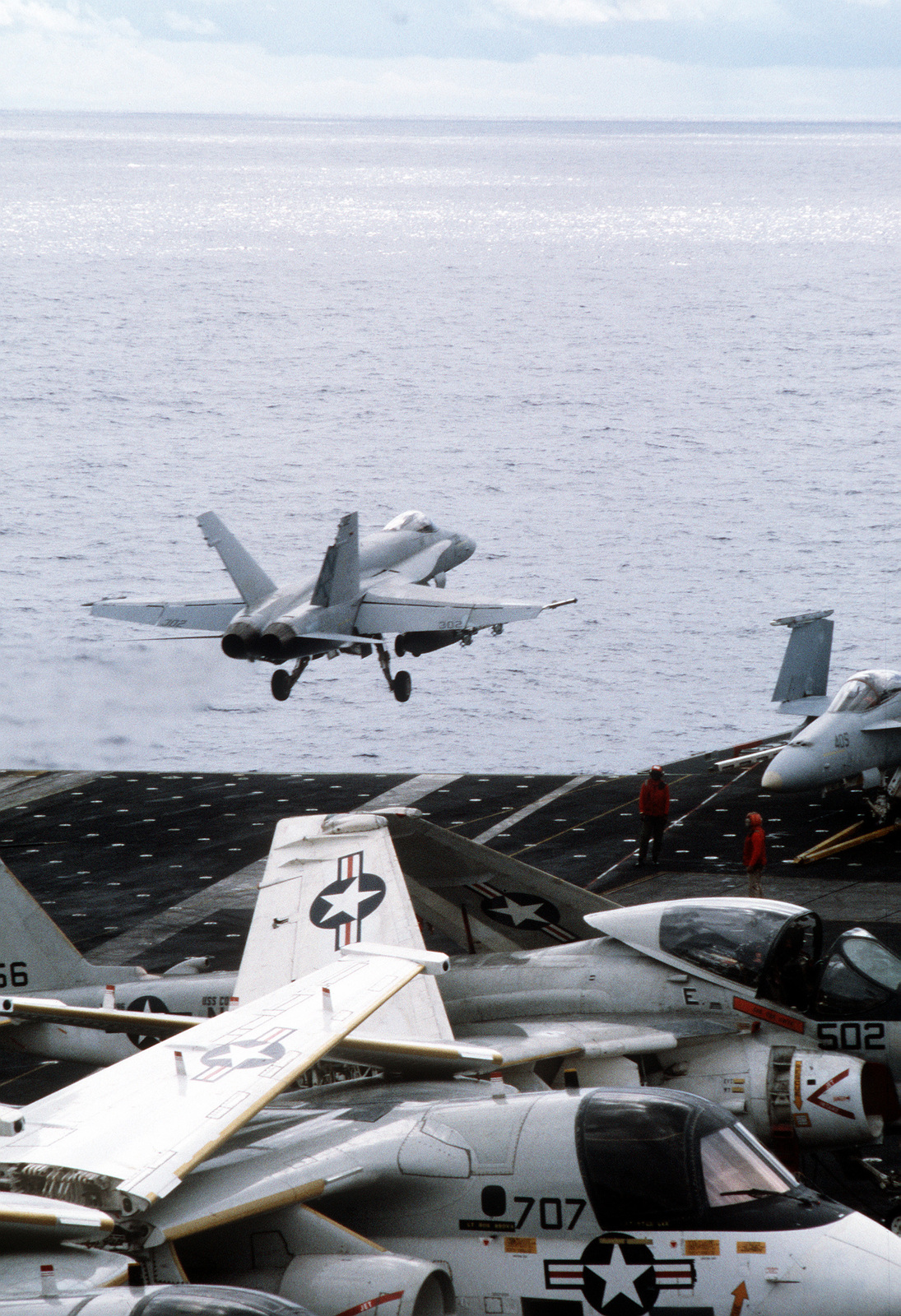 An F/A-18 Hornet aircraft takes off from the aircraft carrier USS CONSTELLATION (CV-64) during Fleet Exercise 8. In the foreground are an S-3A Viking and an A-6E Intruder aircraft