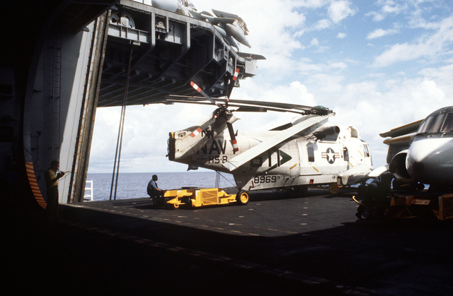 An SD-1D aircraft spotting dolly is used to maneuver an SH-3H Sea King from Helicopter Anti-Submarine Squadron 8 on a lowered elevator aboard the aircraft carrier USS CONSTELLATION (CV 64). On the right is an S-3A Viking aircraft. The carrier is participating in Fleet Exercise 85