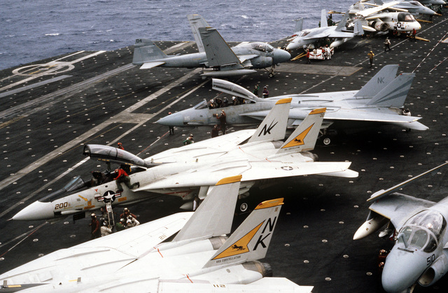 Two F-14A Tomcat aircraft from Fighter Squadron 21 and one from Fighter Squadron 154 (background) are parked on the flight deck of the aircraft carrier USS CONSTELLATION (CV 64) during Fleet Exercise 85. Other aircraft parked on the flight deck include A-6E Intruders, F/A-18A Hornets, and an S-3A Viking