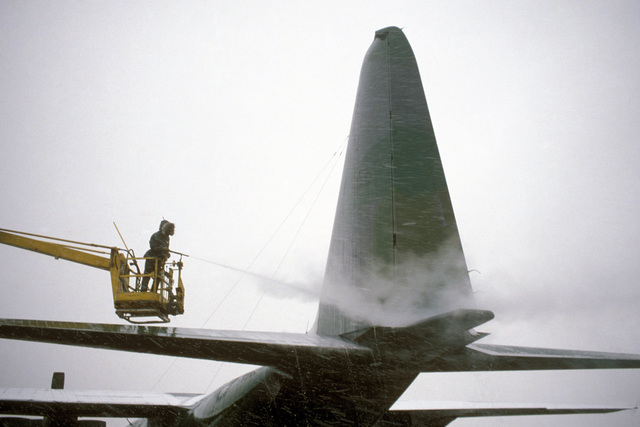 AIRMAN 1ST Class Jerry T. Prudy of the 435th Organizational Maintenance Squadron uses a mixture of hot water and glycol to de-ice the tail section of a C-130 Hercules aircraft. He is in a cherry picker on an MB-1 de-icing vehicle