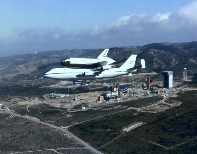An air-to-air left side view of the space shuttle orbiter Discovery atop a NASA Boeing 747 carrier aircraft as it flies over the Space Launch Complex No. 6