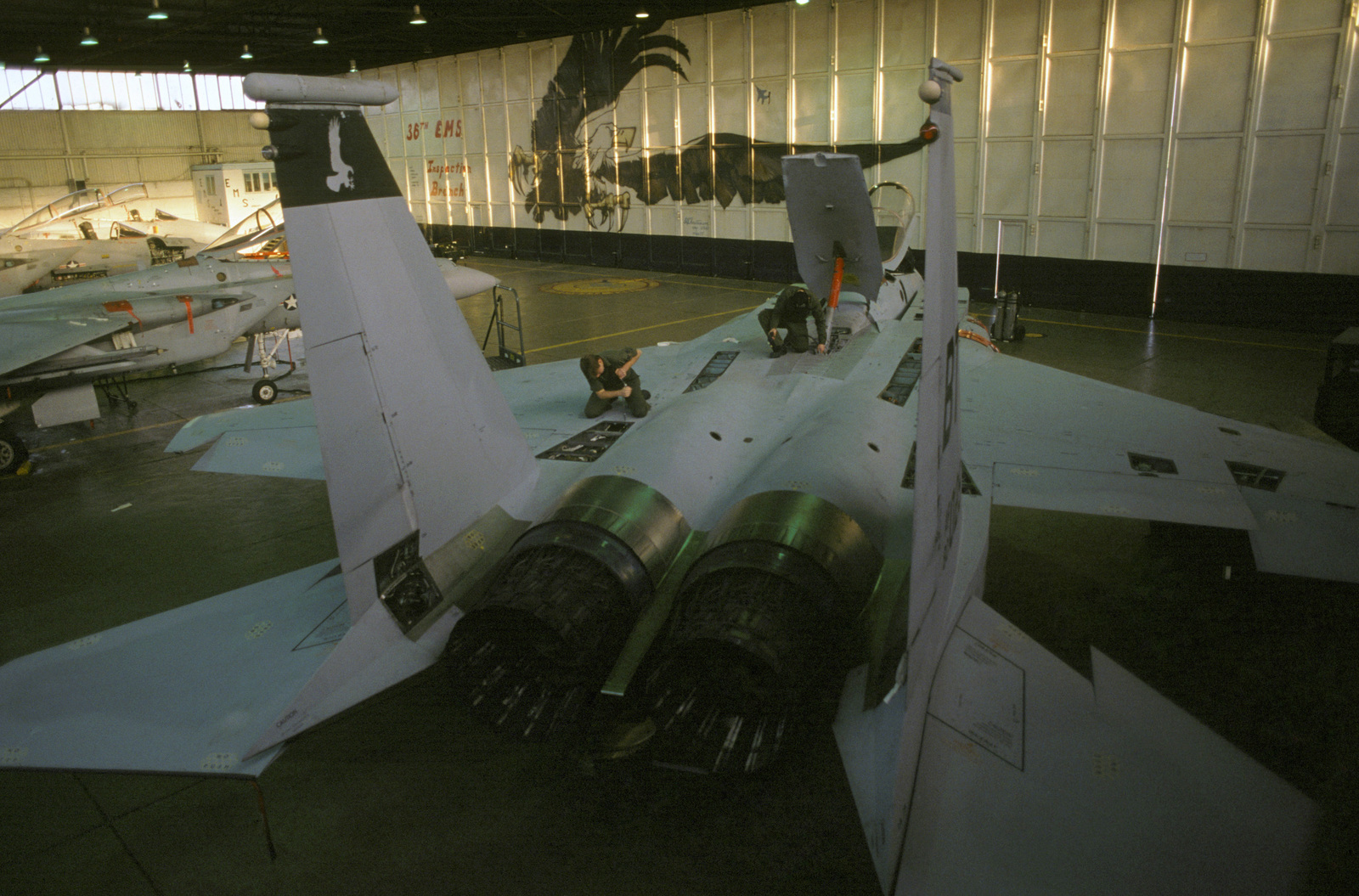 An F-15C Eagle aircraft undergoes a 100-hour post flight inspection in the phase hangar