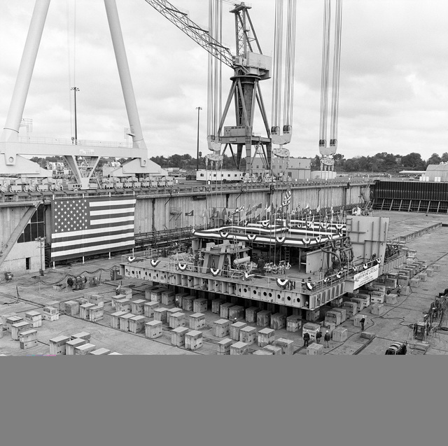 A keel section for the nuclear-powered aircraft carrier USS ABRAHAM LINCOLN (CVN 72) is lowered into place in preparation for the keel laying ceremony at Newport News Shipbuilding and Drydock Company