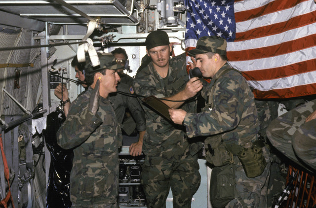 First Lieutenant David Martinez cites the oath of enlistment to reenlistee SENIOR AIRMAN Doug Fouchee aboard a C-130 Hercules aircraft en route to Nellis Air Force Base, Nevada. STAFF Sergeant Phillip Fretwell (center) assists by holding up the United States flag