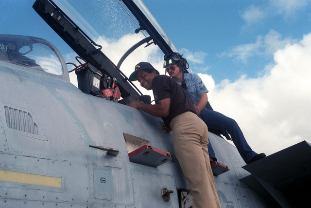 Country singer Charlie Pride is shown the cockpit of an F-14 Tomcat aircraft by Aviation Electronics Technician First Class Rick Seley of the Fighter Squadron 111. The entertainer is aboard the nuclear-powered aircraft carrier USS CARL VINSON (CVN 70) to film a holiday message for the Armed Forces Radio and Television Service