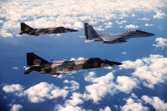 An air-to-air right side view of a 12th Tactical Fighter Squadron F-15 Eagle aircraft in formation with two Japanese Air Self-Defense Force F-1 aircraft during Exercise Cope North 85-1. The F-1s are equipped with AIM-9 Sidewinder missiles on the wing tips
