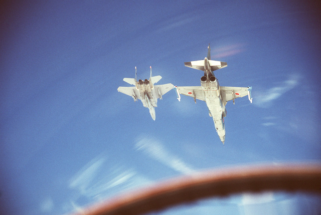 An air to air view of a 12th Tactical Fighter Squadron F-15 Eagle aircraft, left, and a Japanese Air Self Defense Force F-1 aircraft in formation during Exercise COPE NORTH 85-1. The F-1 is armed with AIM-9 Sidewinder missiles on the wing tips