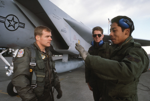 Captain (CPT) Ray Lunger, a 12th Tactical Fighter Squadron pilot, talks with crew chief Sergeant (SGT) Marc Calibb, foreground, and SENIOR AIRMAN (SRA) Terry Barr about the performance of his F-15 Eagle aircraft during Exercise COPE NORTH 85-1