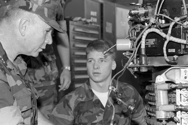 Commandant of the Marine Corps, General (GEN) Paul X. Kelly (left), questions Lance Corporal (LCPL) D. J. Qusada, a member of the Helicopter Engine Repair Unit, on his working knowledge of the TAC-1EL5 overdrive motor coupler system