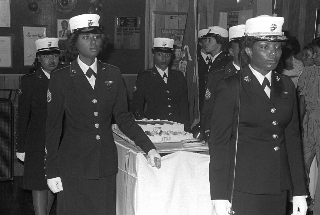 The first black woman Marine cake detail at the Monfort Point Marine Association (MPMA) Marine Corps birthday ball includes STAFF SGT. V. Milton, SGT. D. Sanders, (left to right foreground; CPL. M. Clemmons and Lance CPL. R. Jordan, (left to right background). The woman Marine leading the detail is unidentified