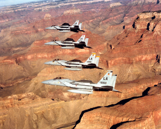 An air-to-air left side view of four F-15 Eagle aircraft in echelon formation. The aircraft are assigned to the 405th Tactical Training Wing, Luke Air Force Base, Ariz