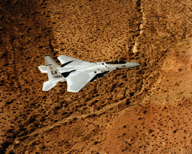 An air-to-air right side view of an F-15 Eagle aircraft from the 555th Tactical Fighter Training Squadron, 405th Tactical Training Wing, Luke Air Force Base, Arizona. The aircraft is equipped with AIM-9 Sidewinder missiles on a wing pylon and fuselage-mounted Sparrow (AIM-7) missiles