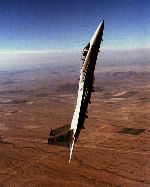 An air-to-air right side view of an F-15 Eagle aircraft in a steep climb. The aircraft, assigned to the 555th Tactical Fighter Training Squadron, 405th Tactical Training Wing, Luke Air Force Base, Arizona, is equipped with AIM-9 Sidewinder missiles on a wing pylon and fuselage-mounted Sparrow (AIM-7) missiles