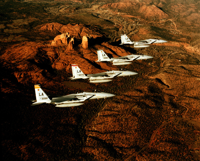 An air-to-air right side view of four F-15 Eagle aircraft in echelon formation. The aircraft are assigned to the 405th Tactical Training Wing, Luke Air Force Base, Arizona