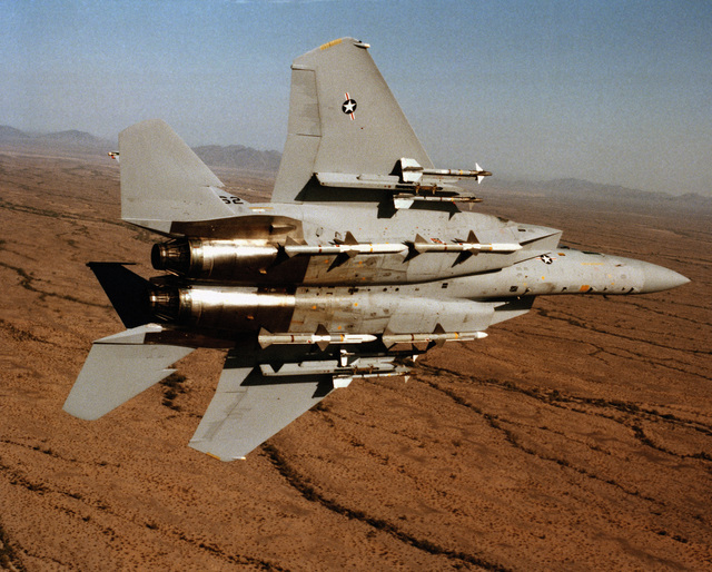 An air-to-air underside view of an F-15 Eagle aircraft from the 555th Tactical Fighter Training Squadron, 405th Tactical Training Wing, Luke Air Force Base, Arizona, banking to the left. The aircraft is equipped with four AIM-9 Sidewinder missiles on the wing pylons and four fuselage-mounted AIM-7 Sparrow missiles