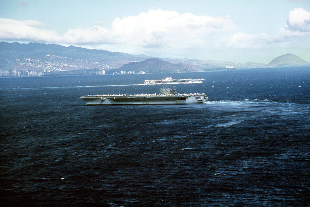 Aerial port beam view of the nuclear-powered aircraft carrier USS CARL VINSON (CVN 70) entering port. In the background another aircraft carrier is departing port