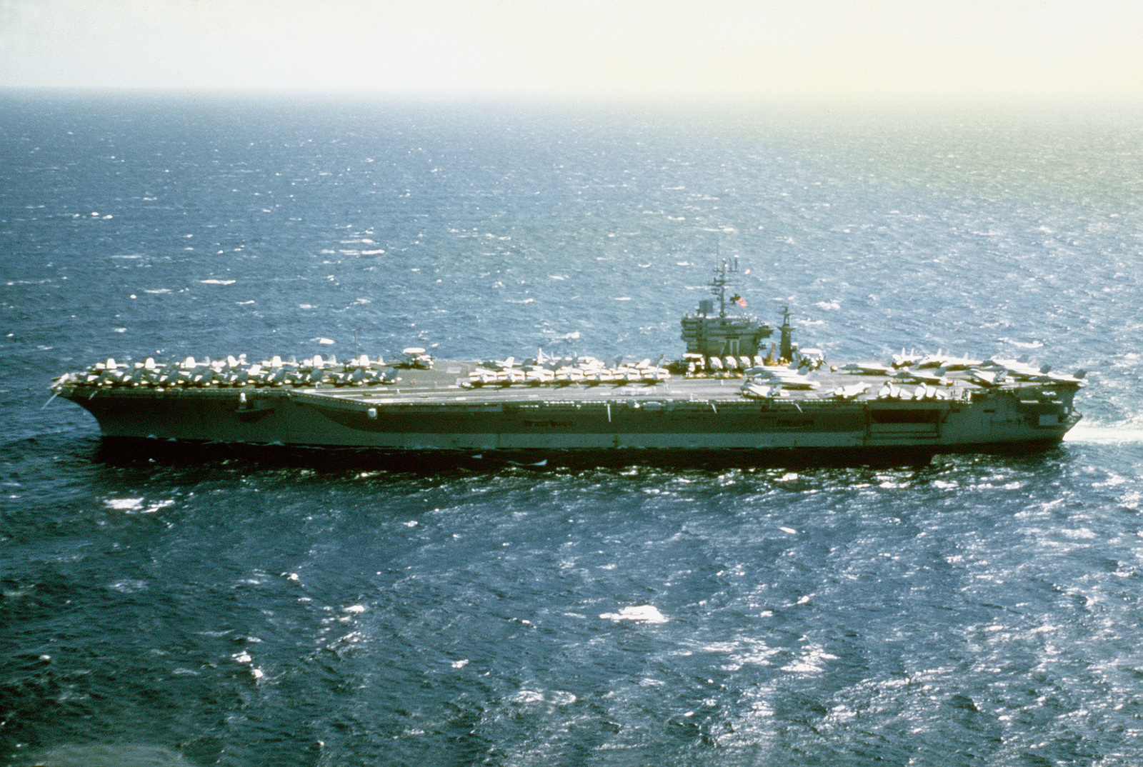 Aerial port beam view of the nuclear-powered aircraft carrier USS CARL VINSON (CVN-70) approaching Pearl Harbor, Hawaii