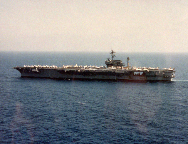 Aerial port beam view of the aircraft carrier USS KITTY HAWK (CV 63) underway. (Substandard image)