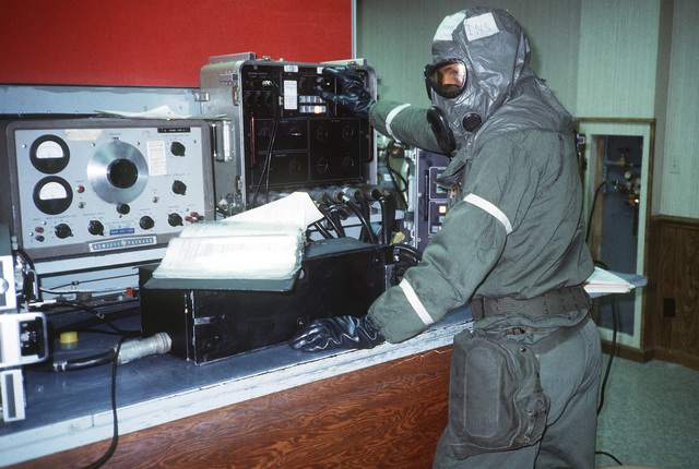 A technician wearing nuclear, biological and chemical (NBC) gear operates test equipment during a 4th Tactical Fighter Wing chemical warfare evaluation