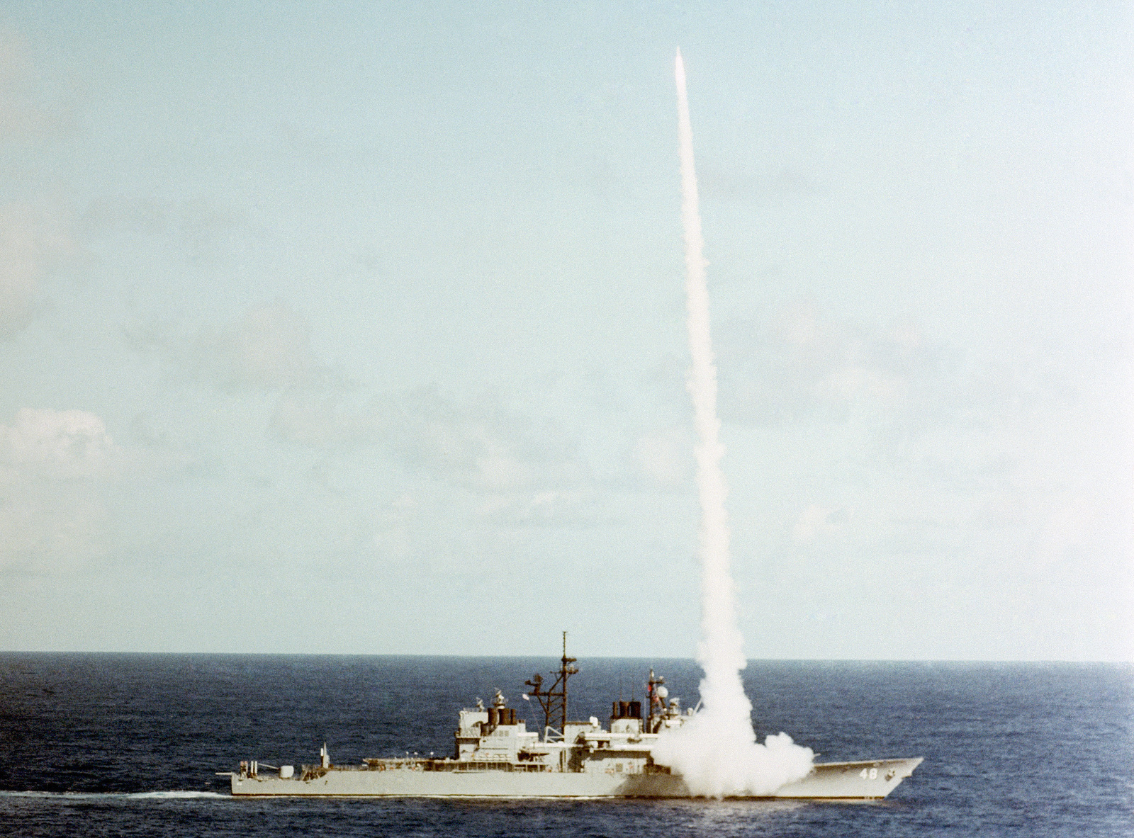 An aerial starboard beam view of the Aegis guided missile cruiser USS YORKTOWN (CG 48) firing an RIM-66 Standard (SM-2) medium range guided missile