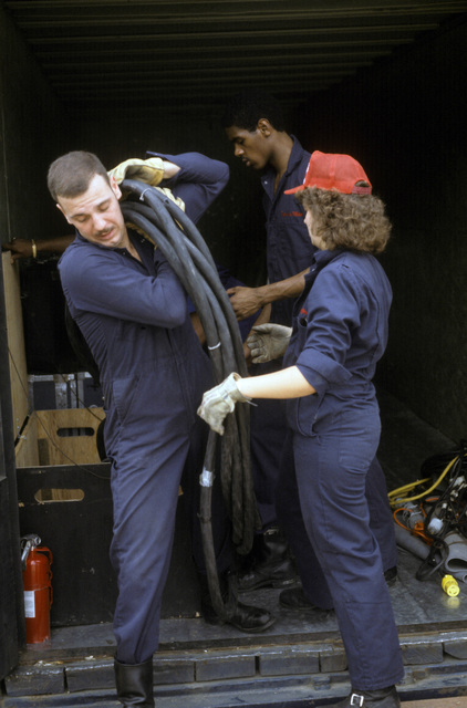 Technical director STAFF Sergenat (SSGT) Jerry Kealler and other Tops in Blue cast members unload a cable from an equipment truck. The group includes Air Force personnel who entertain Air Force members and their families around the world