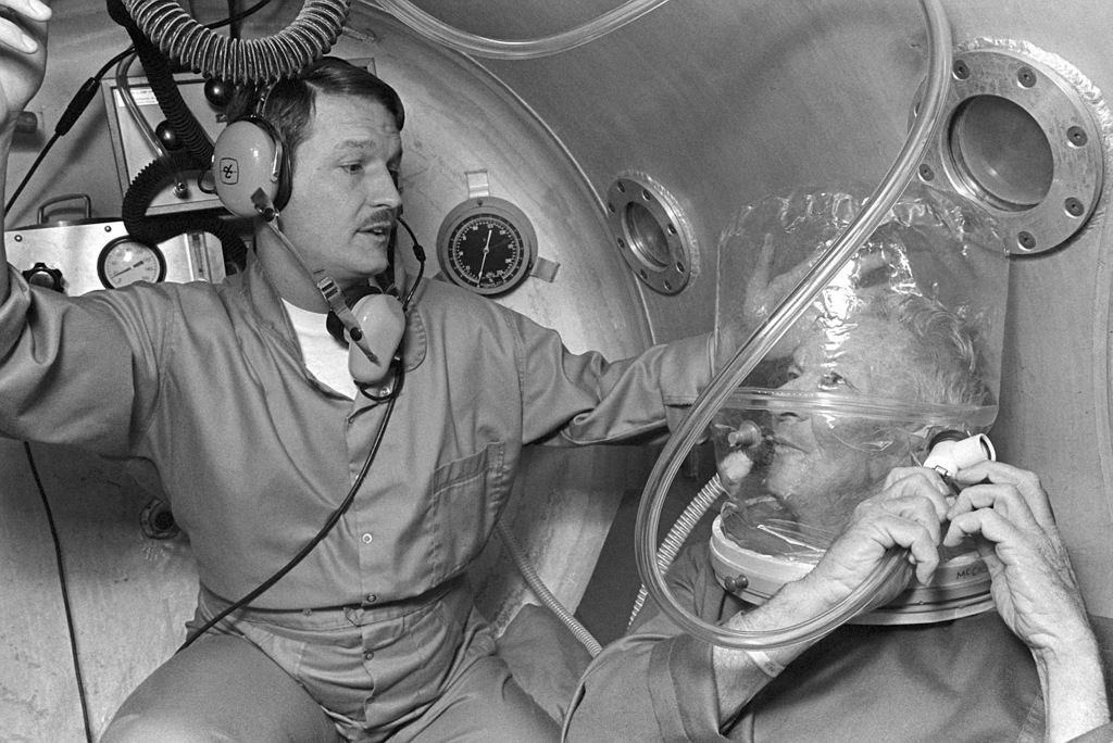 Captain (CPT) William D. Stanford treats a patient in the hyperbaric chamber. The patient is undergoing treatment to heal an open wound caused by cancer surgery