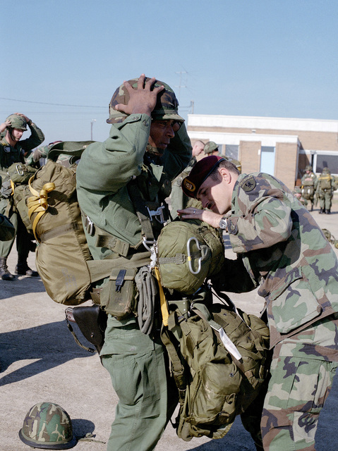 Captain (CPT) Edward D. Clark, Commander, Company C, 509th Infantry, (left), receives a jump master's physical inspection by Sergeant First Class (SFC) Ralph K. Jeffers, Company C, 509th Infantry, prior to jumping during an Army and Air Force Training exercise
