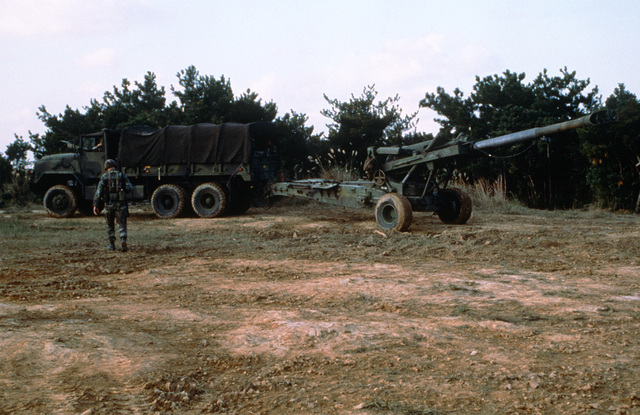 A Marine walks toward an M35 6 1/2 ton cargo truck as preparations are made to tow a 155mm howitzer following a live fire exercise at Camp Hansen