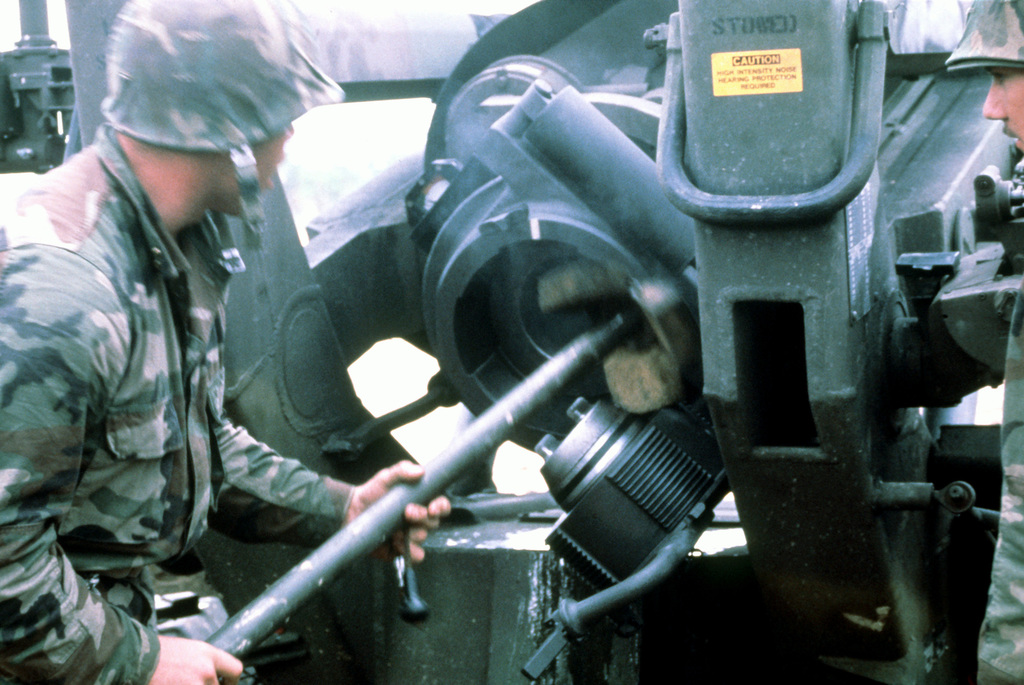 A member of Btry. F, 2nd Bn., 12th Marines, swabs the barrel of a 155mm howitzer after firing. The Marines are participating in a live fire exercise at Camp Hansen
