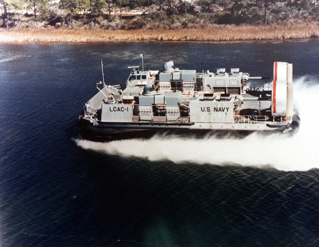 An aerial port bow view of the first production air cushion landing craft (LCAC 1) undergoing sea trials. The LCAC carries a 60-ton payload and is designed to lift equipment organic to the Marine Air-Ground Task Force. It will replace current pre-World War II landing craft scheduled for retirement in the next decade