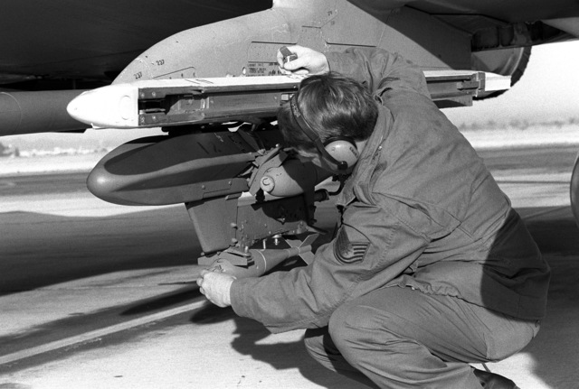 Technical Sergeant Tittus removes bomb blocks from BDU-33 practice bombs mounted on the wing pylon of an RF-4C Phantom II aircraft druing a prefight check