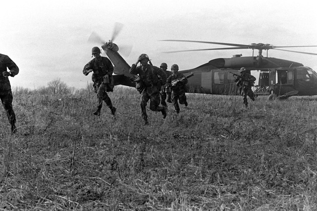 Marine reserves of Co. I, 3rd Bn., 24th Marines, 4th Mar. Div., run for cover after disembarking from U.S. Army UH-60 Black Hawk (Blackhawk) helicopters during a weekend drill