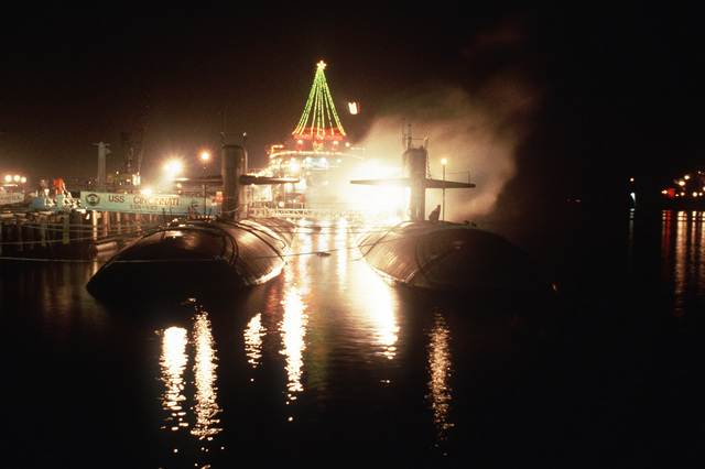 Christmas lights are used to decorate ships that are in port for Christmas. The nuclear-powered attack submarine USS CINCINNATI (SSN-693) is in the foreground to the left
