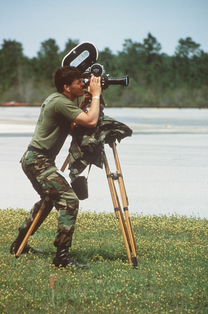 Sergeant (SGT) Rick Trinque, Detachment Seven, 1361st Audiovisual Squadron, films activity on a runway during Operation BIG SQUIRT