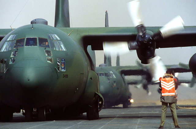SENIOR AIRMAN Eric Palmer South Korea....A plane director guides C-130 Hercules aircraft to parking spaces on the flight line at Yeo Ju airstrip, where Korean Marines will be offloaded during the joint U.S./South Korean exercise Team Spirit '84. OFFICIAL U.S. AIR FORCE PHOTO (RELEASED)AVAILABLE ON CD