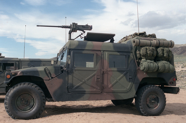 A left side view of a US Army M998 High-Mobility Multipurpose Wheeled Vehicle equipped with an M2 .50 caliber machine gun. Field packs are attached on the rear of the vehicle