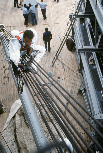 A sailor aboard the battleship USS IOWA (BB 61) greases the cables of a boom during Exercise OCEAN SAFARI '85